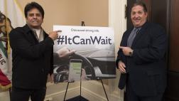 Assemblymember Frazier and actor Erik Estrada next to a car graphic with the hashtag #ItCanWait